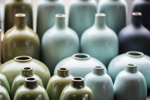Arranged in rows of pale blue China bottles